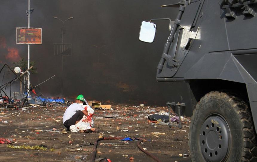 Dois protestantes pró-Morsi no cenário de destruição do Cairo AP Photo/Ahmed Gomaa