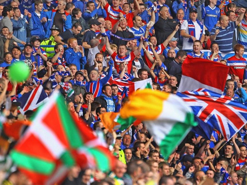 Foto da arquibancada durante um Old Firm. Note em primeiro plano os torcedores verdes, com bandeiras da Irlanda e do País Basco, em solidariedade, visto como país também dominado por estrangeiros. Do outro lado, de azul, os torcedores do Rangers, com a Union Jack.