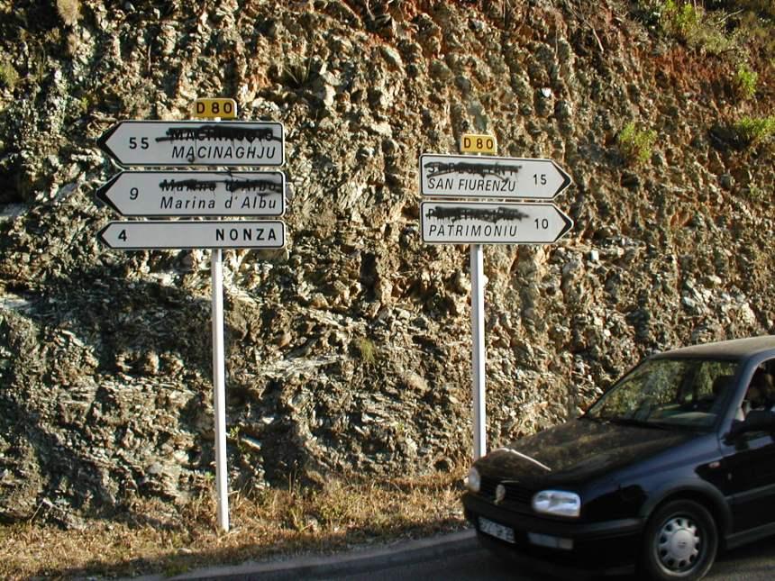 As placas bilíngues da ilha costumam ter os letreiros em francês pichados.