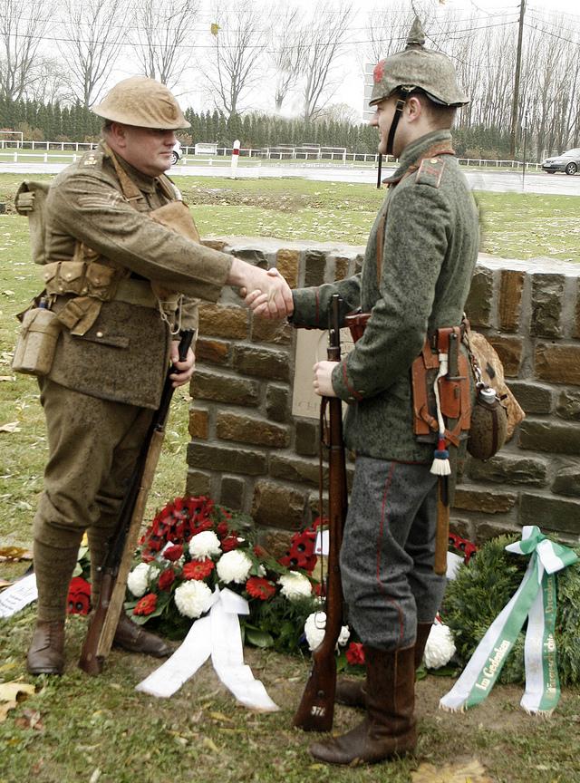 Dois descendentes de veteranos inauguram, vestidos à caráter, um monumento que homenageia a Trégua de Natal.