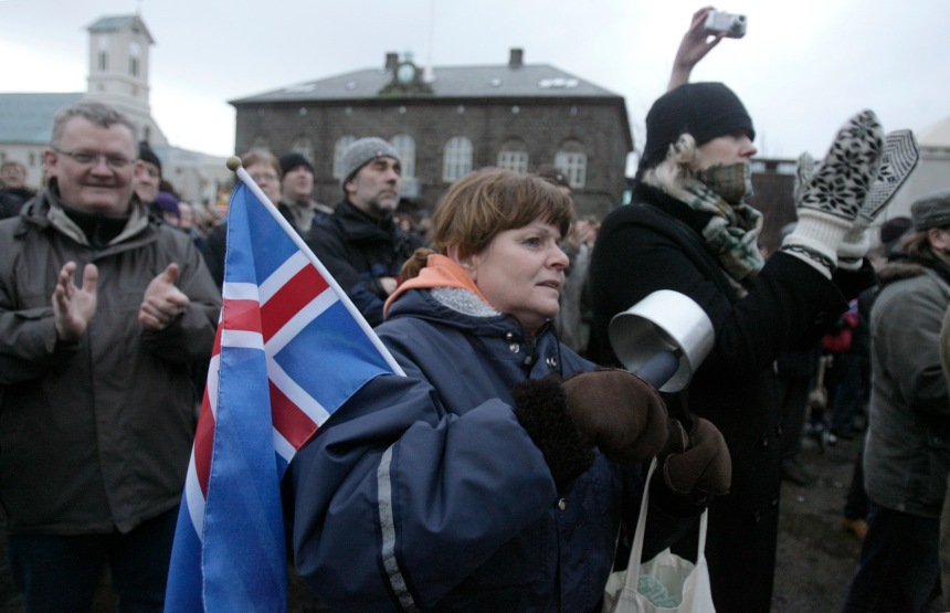 "A woman holds a flag of Iceland as she gathers during a peaceful protest near Iceland's Parliament house in Reykjavik January 24, 2009. A day after saying he would quit, Iceland's Prime Minister Geir Haarde voiced ""contempt"" on Saturday for some of the actions by banks that triggered the country's economic collapse. Iceland, one of the richest countries in the world in 2007, plunged into crisis in October when it fell victim to the global credit crunch. Its currency collapsed as its financial system imploded. To stay afloat, it negotiated a $10 billion aid package crafted by the International Monetary Fund and effectively froze trade in its currency.    REUTERS/Ints Kalnins (ICELAND)"