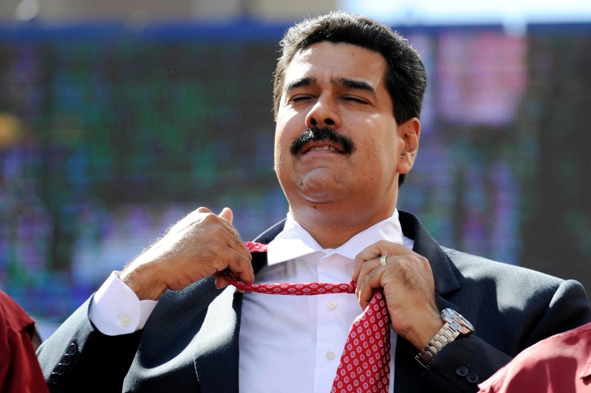 Venezuelan President Nicolas Maduro unties his tie during a rally in Caracas on November 12, 2013. Venezuela's ruling party eyed a vote Tuesday to pave the way for Maduro to govern by decree, broadening his powers, during an inflationary crisis a month before crucial municipal elections. AFP PHOTO/Leo RAMIREZ (Photo credit should read LEO RAMIREZ/AFP/Getty Images)
