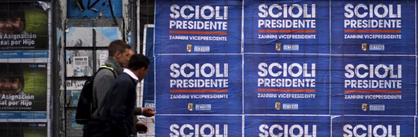 People walk next to posters advertising presidential candidate Daniel Scioli in Buenos Aires October 19, 2015. The Argentinian ruling party's candidate Scioli is primed to win the presidential election outright on October 25, with a commanding lead over his nearest rivals, two polls published in local papers on Sunday showed. His closest rival, Mauricio Macri, the center-right mayor of Buenos Aires city, is seen getting 28 percent of the vote in the election, according to the poll. REUTERS/Marcos Brindicci