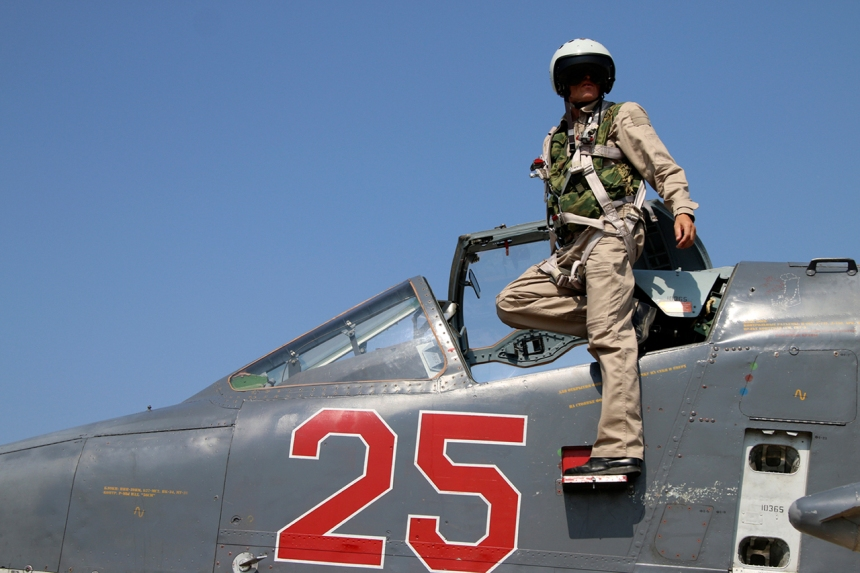 In this photo taken on Saturday, Oct. 3, 2015, Russian army pilot poses at a cockpit of SU-25M jet fighter at Hmeimim airbase in Syria. Russia has insisted that the airstrikes that began Wednesday are targeting the Islamic State group and al-Qaida's Syrian affiliates, but at least some of the strikes appear to have hit Western-backed rebel factions.(AP Photo/Alexander Kots, Komsomolskaya Pravda, Photo via AP)