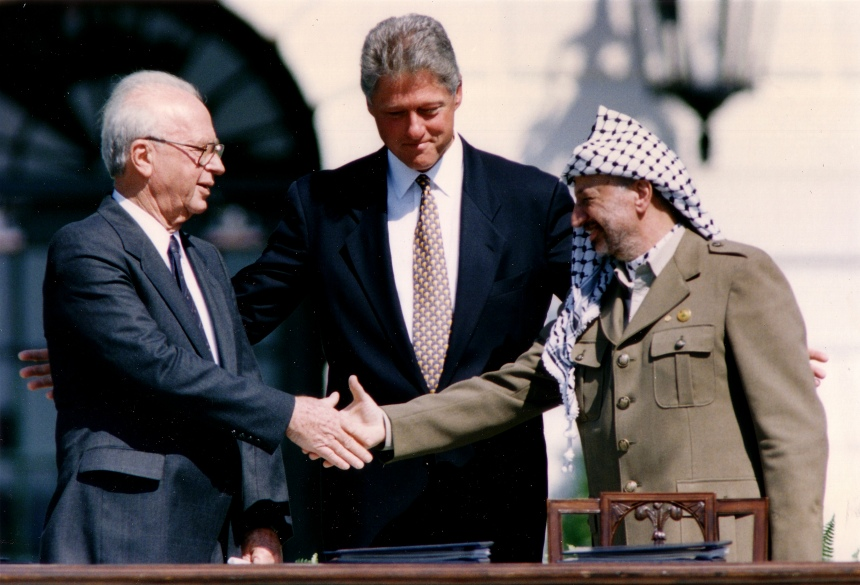 PLO Chairman Arafat shakes hands with Israeli PM Rabin after the signing of the Israeli-PLO peace accord, in Washington